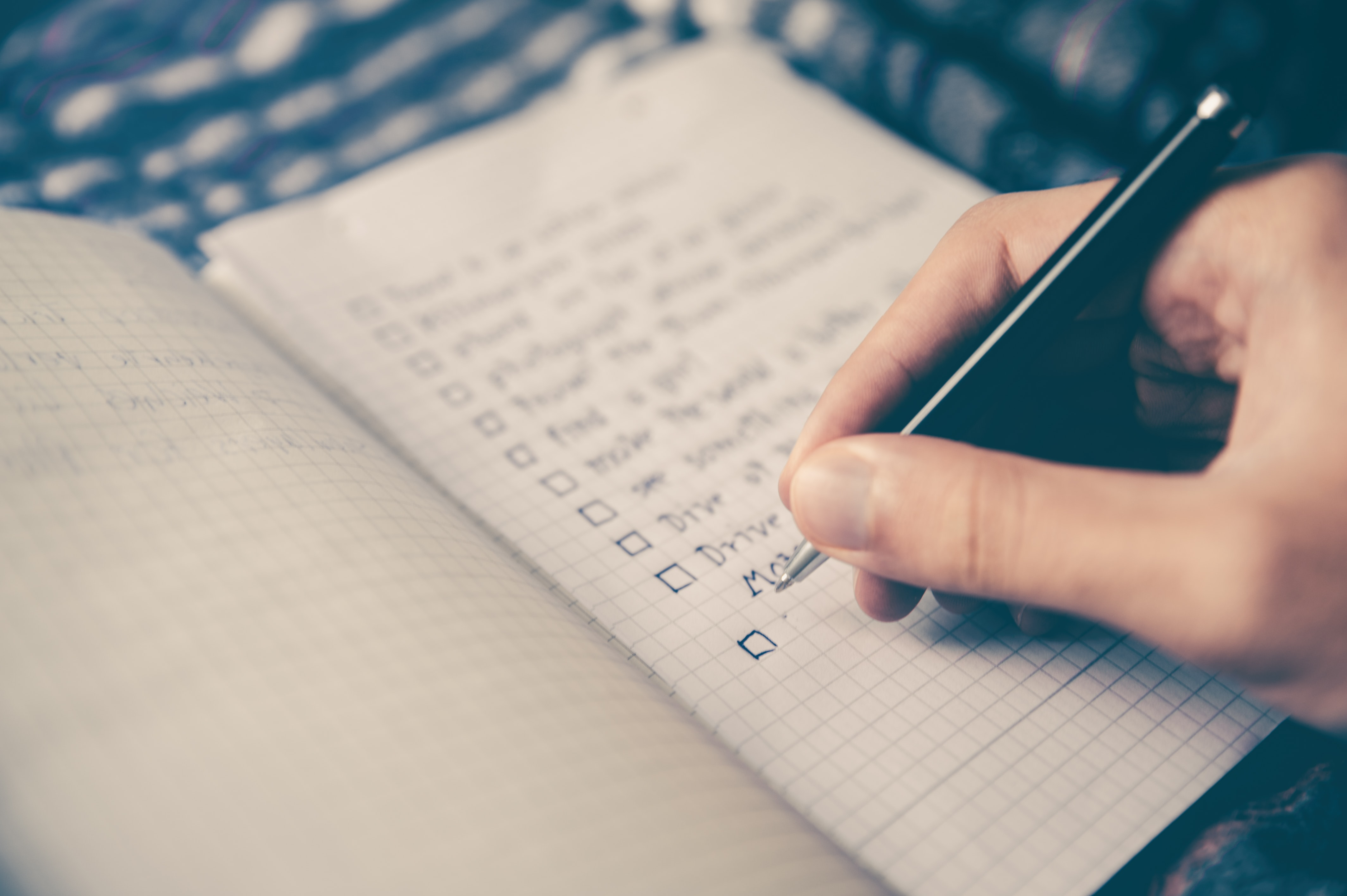 A person writing out a checklist or todo list.