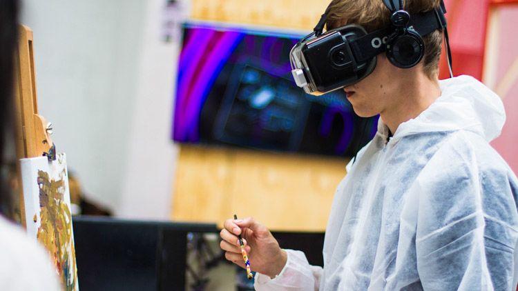 Young man painting using Virtual Reality headgear.
